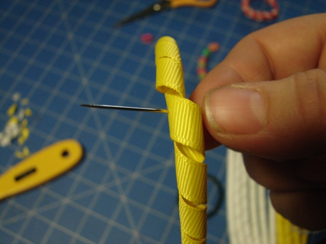 push your needle and thread through the middle of the ribbon